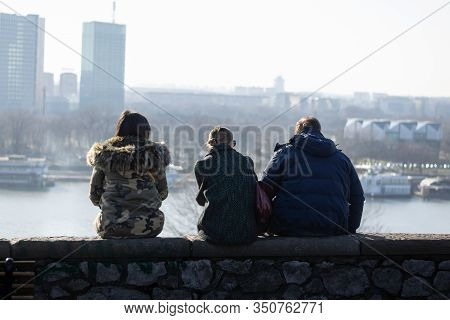 People Enjoying City View In Belgrade. Young People In City. People Sitting Together On Wall Enjoyin