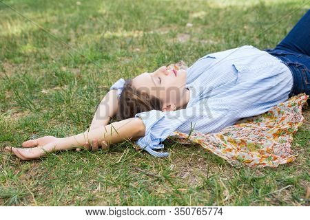 Relaxed Young Woman Lying On Headkerchief On Ground In Park. Beautiful Lady Relaxing Outdoors. Leisu