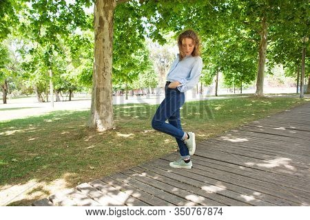Relaxed Young Woman Standing On One Leg In Spring Park. Careless Lady Wearing Casual Clothing Standi