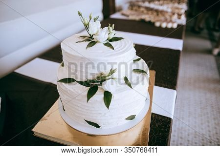 White Wedding Cake With Buttercream Icing  Decorated With White Roses And Green Branches With Leaves