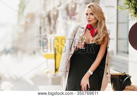Curly Blonde Woman In Black Pleated Dress Celebrating Something With Champagne. Outdoor Portrait Of