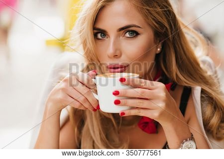 Close-up Portrait Of Stunning Blue-eyed Lady Chilling In Cafe And Drinking Hot Coffee. Photo Of Refi