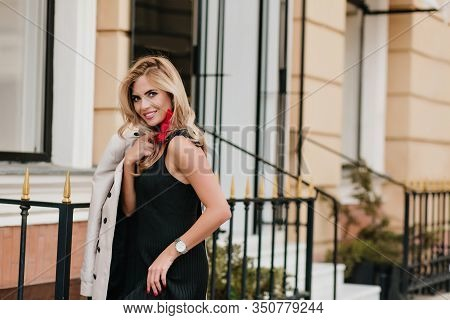 Slim Glad Woman In Trendy White Wristwatch Laughing While Posing Beside Store. Outdoor Portrait Of S