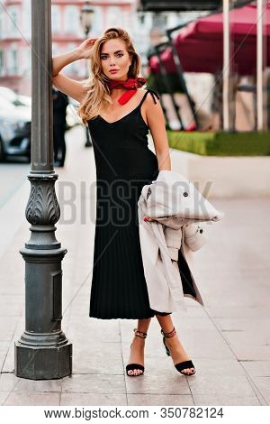 Stylish Tanned Girl In Black Dress And Red Neckerchief Posing Near Iron Lamppost. Full-length Portra