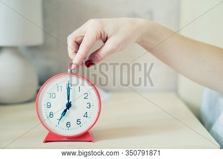 Closeup Of Woman Hand Reaching To Turn Off Classic Red Alarm Clock