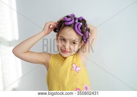 A Little Girl Pretends To Be An Adult Woman Or Her Mommy With Curlers In Her Hair. The Concept Of Ki