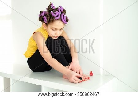 A Little Girl Pretends To Be An Adult Woman With Curlers In Her Hair And Paints Her Toenails With Re