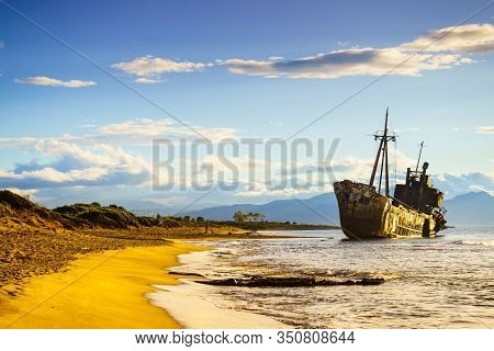 An Old Abandoned Shipwreck, Wrecked Boat Sunken Ship Stand On Beach Coast. Scenic Seascape