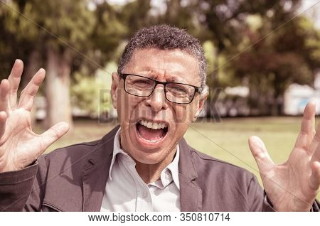Indignant Middle-aged Man Screaming And Raising Hands In Park. Guy Wearing Casual Clothes And Lookin