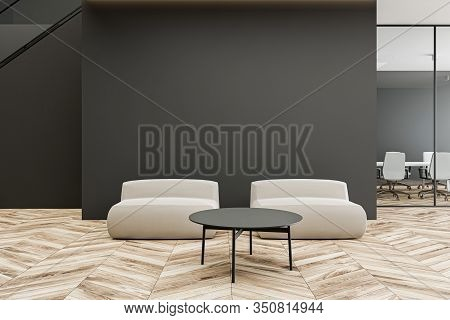 Comfortable White Armchairs Standing Near Round Coffee Table In Modern Office Waiting Room With Dark