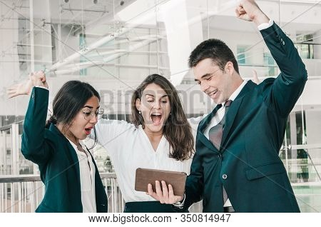 Three Good Looking Colleagues Standing In Office Corridor, Exulting, Receiving Good News, Raising Up