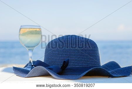 A Glass Of White Wine And A Blue Hat Behind Lagoon Sea. Summer Vacation Concept.beautiful Summer Day