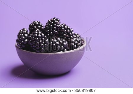 Organic Blackberries In A Bowl, Isolated On A Purple Background. Close-up Of Fresh Blackberries Frui