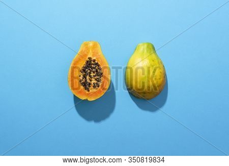 Fresh Papaya Fruit Cut In Half, Isolated On A Blue Background, In Sunlight. Juicy Tropical Fruit. Sw