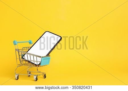Phone With Empty Screen And Shopping Cart On Yellow Background, Space For Text