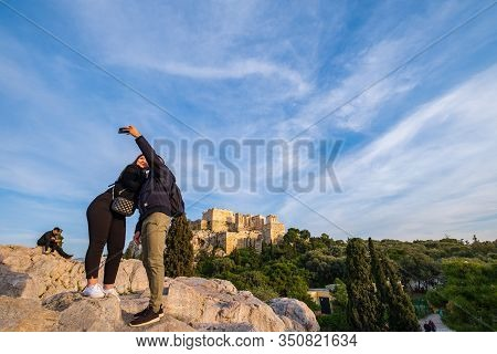 Athens, Greece - January 25, 2020: A Couple Are Taking A Selfie On A Hill Across The Acropolis Rock