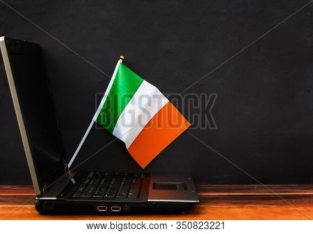 Flag Of Ireland , Computer, Laptop On Table And Dark Background