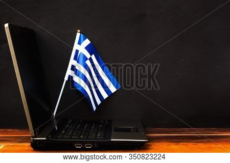 Flag Of Greece , Computer, Laptop On Table And Dark Background