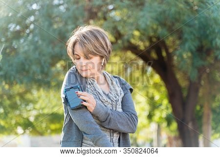 Confident Retired Fit Senior Woman Using Smartphone On Armband In City On Sunny Day
