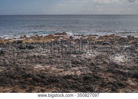 Kauai, Hawaii, Usa. - January 11, 2012: Black Lava Rocks At Kawailoa Beach In Front Of Azure And Gra