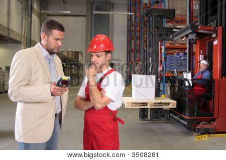 Boss Talking To Worker In Factory