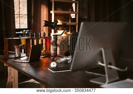 A Mirrorless Digital Camera On Gimbal Stabiliser, Unique Table Lamp, Computer, Laptop Are On A Woode