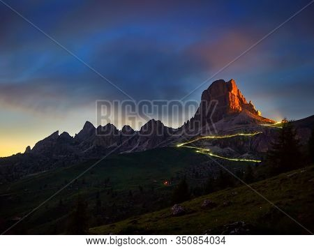 Milky Way above the mountains at night in summer. Landscape with alpine mountain valley, blue sky with milky way and stars, buildings on the hill, rocks. Aerial view. Passo di Giau, Dolomites, Italy