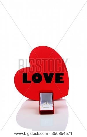 Engagement Ring. Valentines Day Gift. Wedding Ring. Red Heart with the word LOVE and an Engagement Ring;. Isolated on white. Room for text. Clipping Path. Love is in the air. Happy Valentines Day.