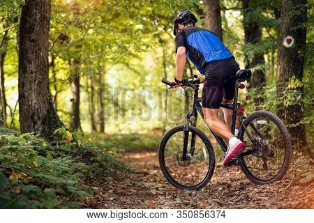 outdoor trail on bike young man riding bike through forest .Spring, nature ,sport concept