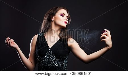 Attractive Young Brunette Woman And A Bottle With A New Fragrance, Use Perfume. Portrait On A Black