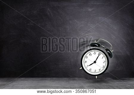 Time Management Concept : Retro Black Alarm Clock Alerting At Seven Clock On Chalkboard Background.