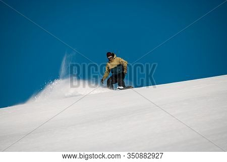 Male Freerider Slides Down On The Mountain Side