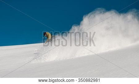 Male Freerider Slides Down The Snowy Mountain Slope