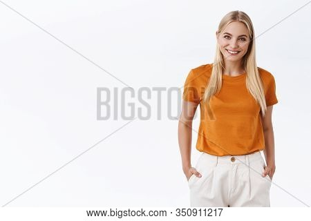Attractive, Stylish Modern Woman With Blond Hair, Wear Orange T-shirt, Hold Hands In Pants Pockets,