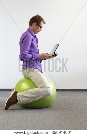 man working with  tablet and sitting  on large stability  ball - exercise in office