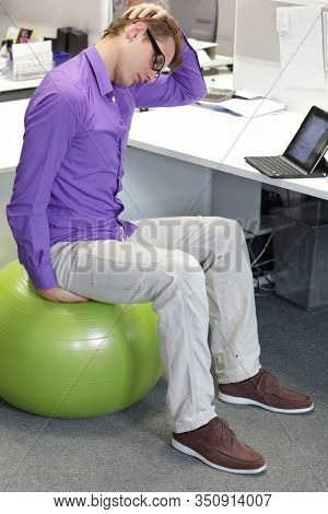 man stretching neck sitting on stability ball in his office