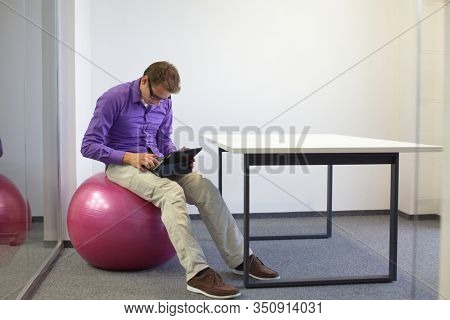 man browsing internet on  tablet and sitting  on large stability  ball - bad sitting posture