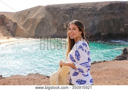 Portrait Of Beautiful Tourist Woman With Playa Papagayo Landscape On Background. Happy Girl With Hat