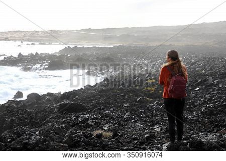 Desolate Volcanic Black Rocks With Lonely Girl. Back View Of Young Woman Standing Reflexive And Sad