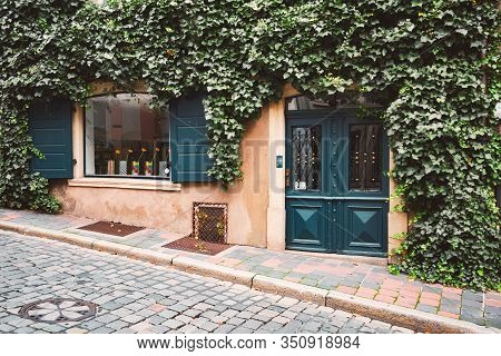 Beautiful Street Shop In Germany, Europe. Lush Green On Facade Of Building, Cobblestone Walkway In F