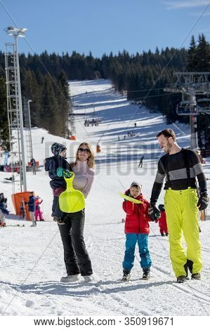 Parents With Children Walking On Snow In Ski Resort. Family Winter Vacation