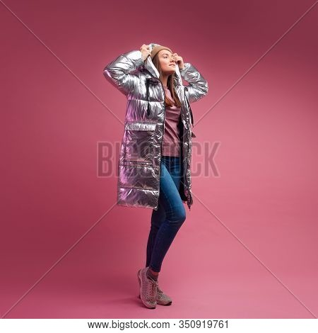 Fashionable And Modern Young Woman In A Puffy Light Down Jacket Throws A Hood Over Her Head. The Jac