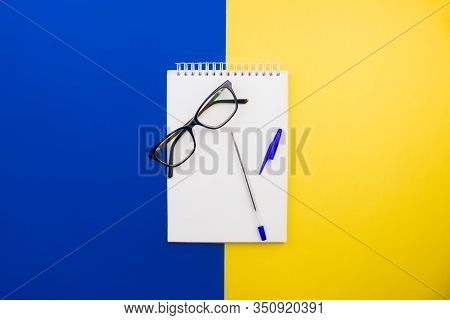Opened Sketchbook With Eyeglasses And Pen Flat Lay On Colorful Yellow And Blue Background Top View W