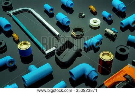Plumbing Tools. Plumber Equipment. Blue Pvc Pipe Fittings, Hacksaw, Glue Can, And Pipe Wrench. House