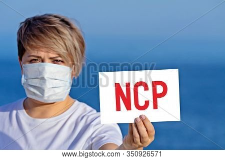 Woman In Surgical Face Mask Holds Blank With Text Ncp That Mean Novel Coronavirus Pneumonia. Concept