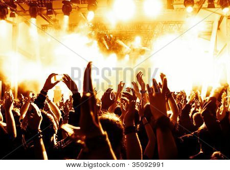 cheering crowd in front of bright yellow stage lights