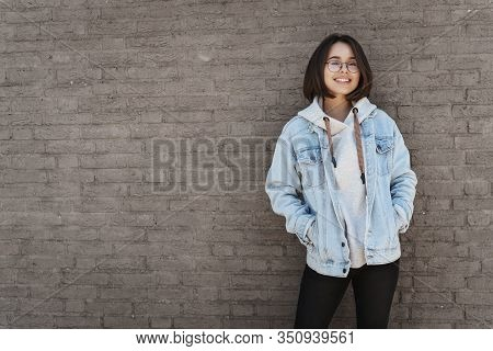 Attractive Young Queer Girl With Short Hair, Wearing Glasses And Streetstyle Clothes, Leaning Brick