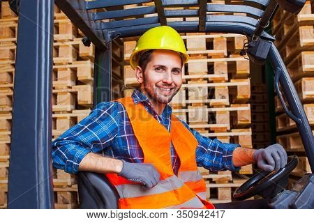 Handsome Smiling Worker Driving Forklift In Warehouse. Woodworking Industry Concept.