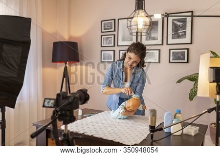 Female Vlogger Making A Video About Brushing Newborn Baby Hair, Parietal Region And Soft Spot Care A