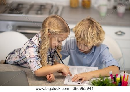 Two Kids Sitting At The Table And Looking Busy While Drawing